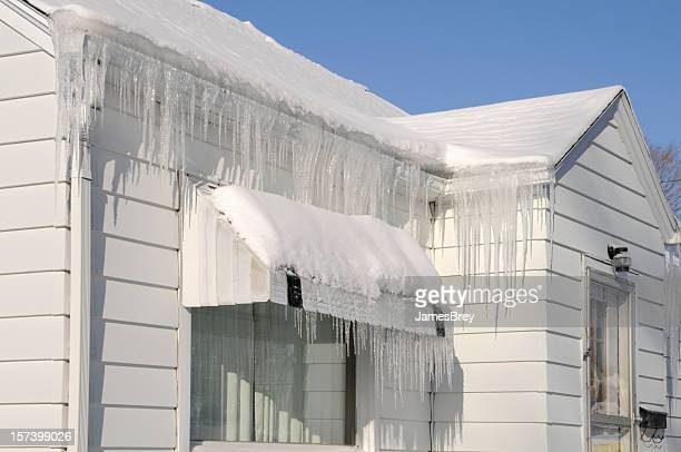 Extreme Icicles, Snow, House Roof After Winter Blizzard; Weather Damage