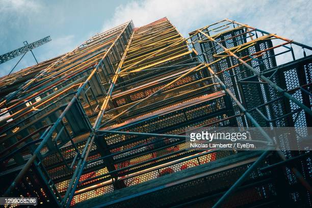 extreme low angle view of scaffolding in front of mural painted building against sky - colónia renânia imagens e fotografias de stock