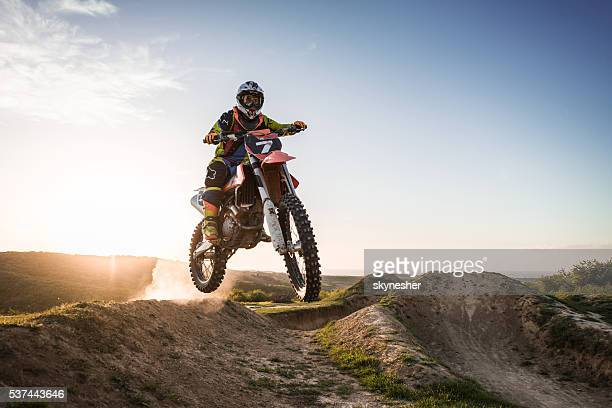 Extreme motorcyclist riding dirt bike off-road at sunset.