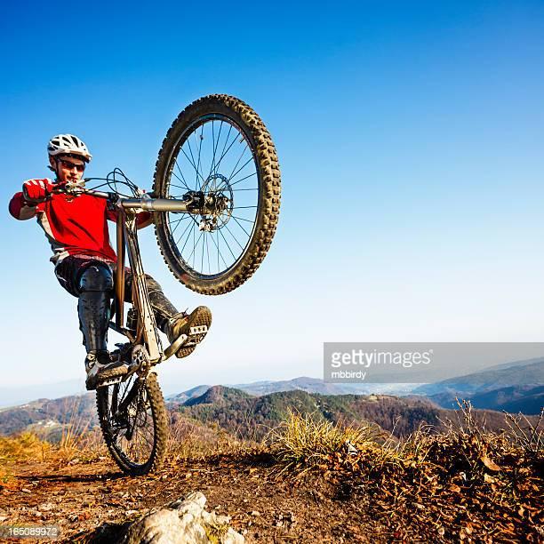 Extreme mountainbiker riding a wheelie