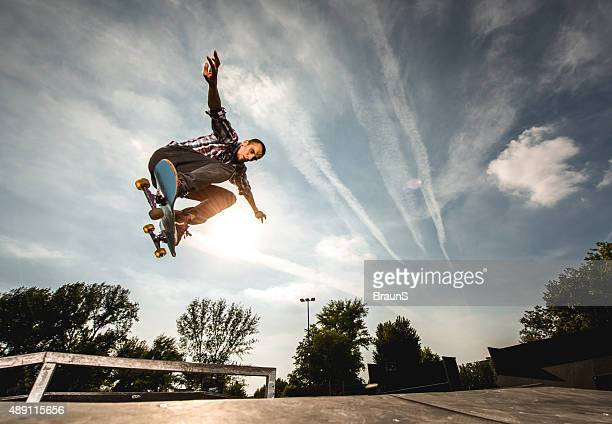 extreme skateboarder in ollie position against the sky. - skating stock photos and pictures