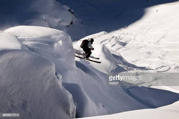 Extreme skier jumping off a spine in the back country mountain