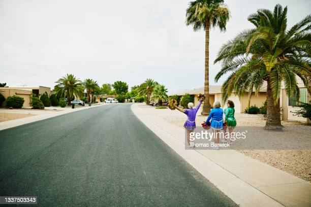 extreme wide shot of senior female cheerleaders walking on sidewalk in neighborhood - mini dress stock pictures, royalty-free photos & images