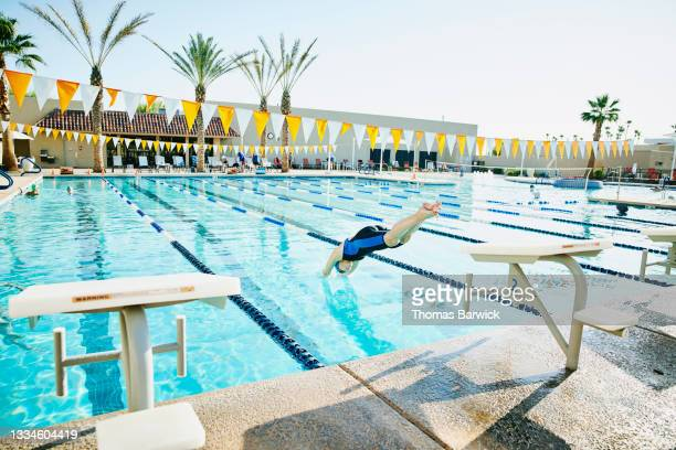 extreme wide shot of senior female swimmer diving into pool during early morning workout - diving into water stock pictures, royalty-free photos & images