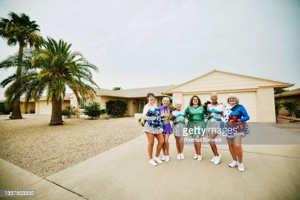 extreme wide shot portrait of smiling senior female cheerleaders embracing after practice - mini dress stock pictures, royalty-free photos & images