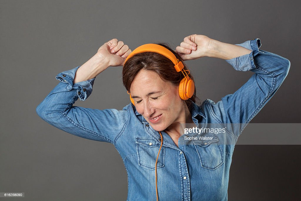 extrovert beautiful middle aged woman with eyes closed enjoying dancing : Foto de stock