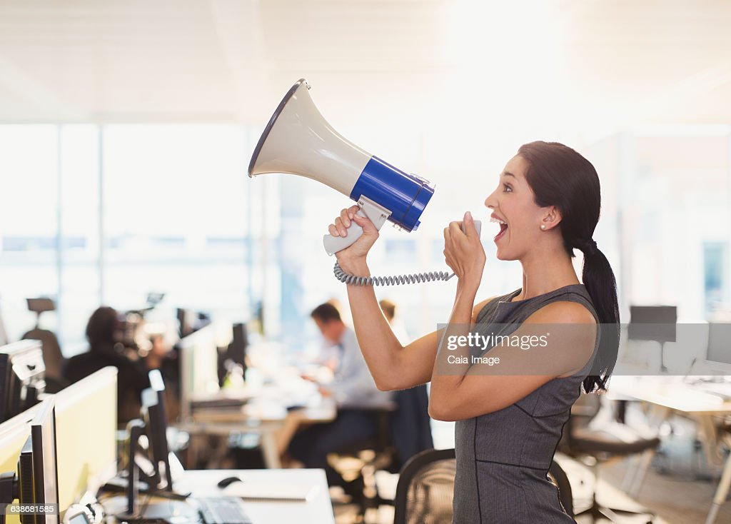 Exuberant businesswoman using megaphone in office : Stock-Foto