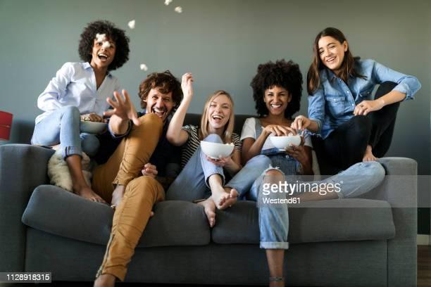 exuberant friends sitting on couch throwing popcorn - televisie kijken stockfoto's en -beelden