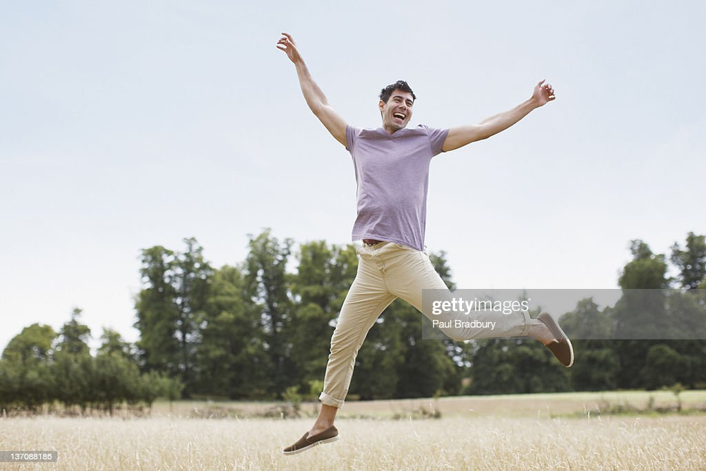 Exuberant man jumping in rural field : Stock Photo