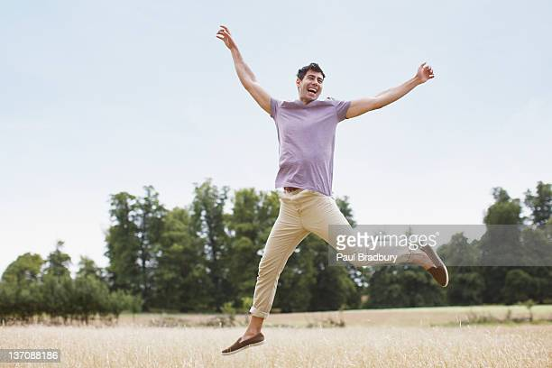 Exuberant man jumping in rural field