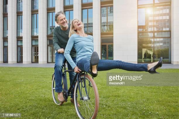 exuberant mature couple riding bicycle on lawn in the city - pedalantrieb stock-fotos und bilder