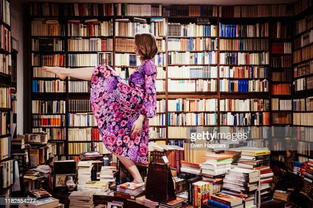 exuberant woman dancing on book stacks in library - library stock pictures, royalty-free photos & images