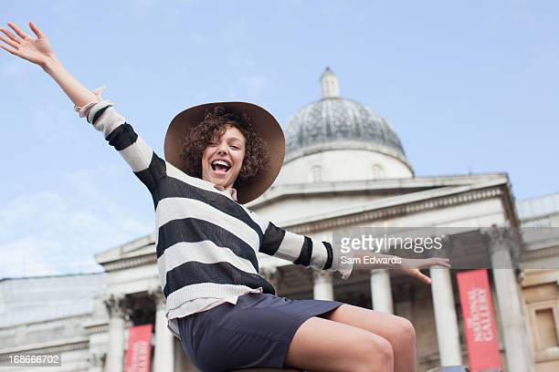 exuberant woman in hat below historical landmark in london - national portrait gallery london stock pictures, royalty-free photos & images