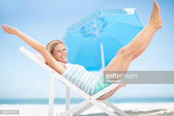 Exuberant woman on a beach chair
