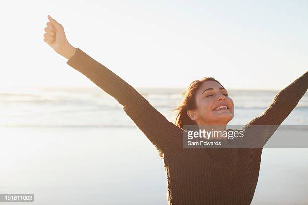 Exuberant woman standing on sunny beach with arms outstretched