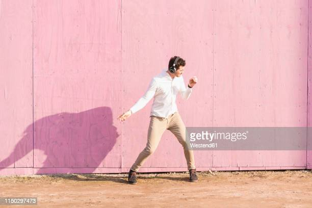 exuberant young man listening to music in front of pink wall - all shirts ストックフォトと画像