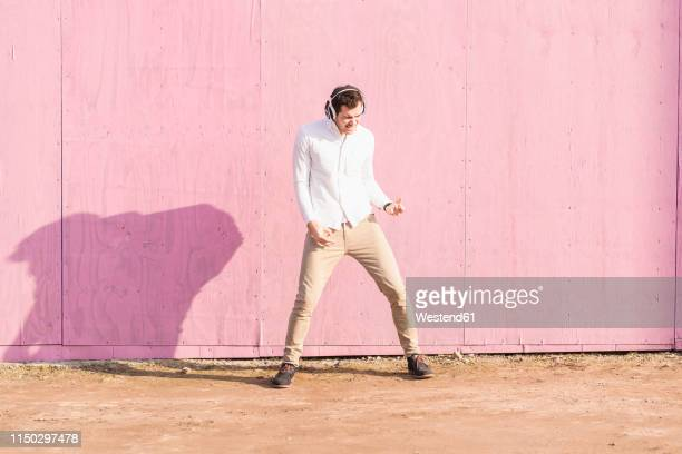 exuberant young man listening to music in front of pink wall - early rock & roll stock pictures, royalty-free photos & images