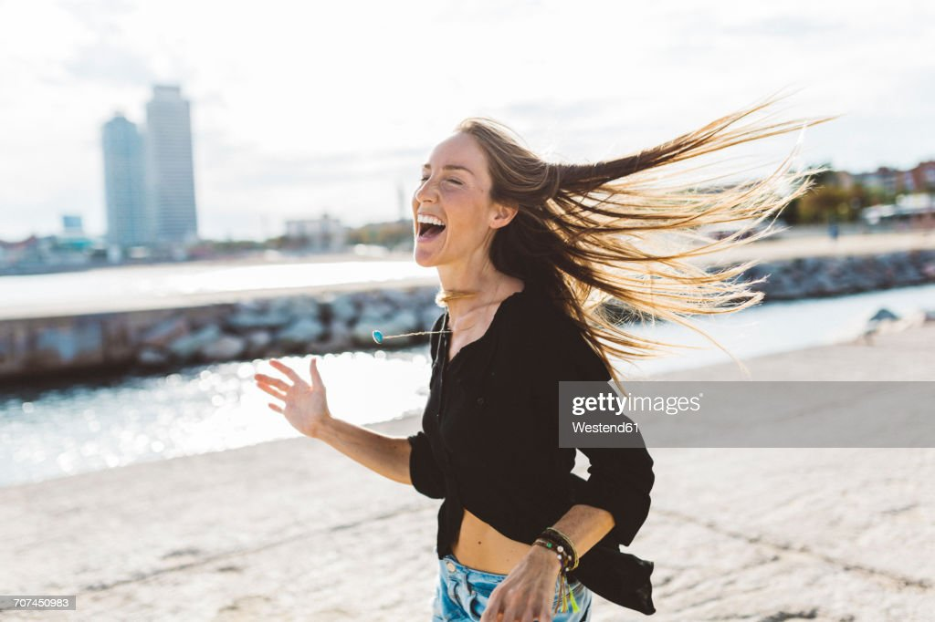 Exuberant young woman at the seafront : ストックフォト