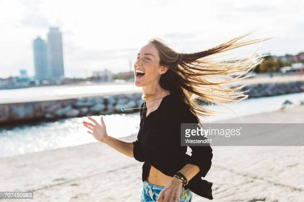 Exuberant young woman at the seafront