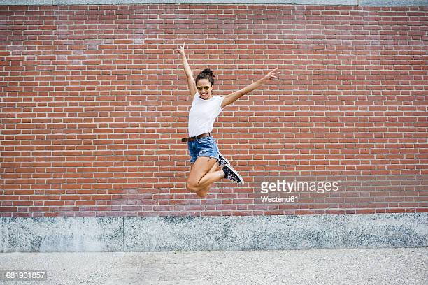 Exuberant young woman jumping in front of a brick wall