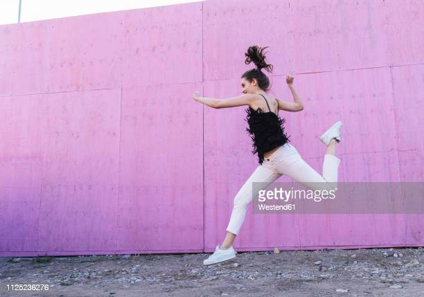 exuberant young woman jumping in front of pink wall - 僅一名年輕女人 個照片及圖片檔