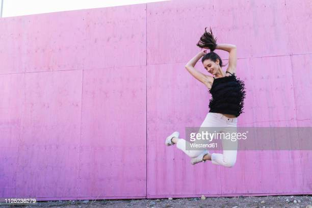 exuberant young woman jumping in front of pink wall - magenta stock pictures, royalty-free photos & images