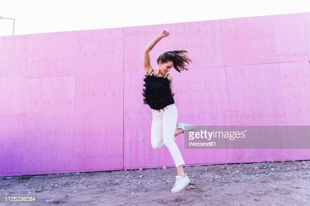 exuberant young woman jumping in front of pink wall - à franges photos et images de collection