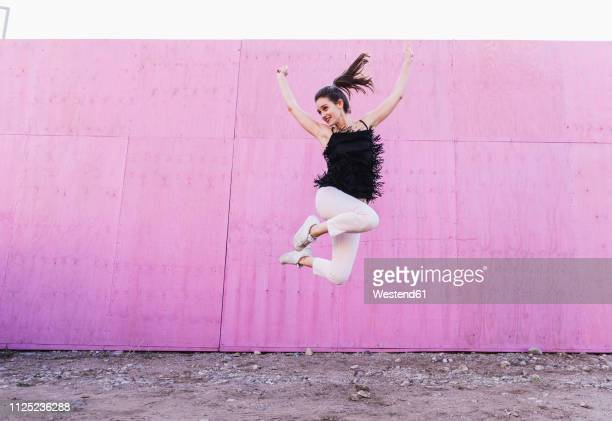 exuberant young woman jumping in front of pink wall - leichter stock-fotos und bilder