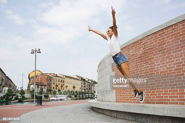 Exuberant young woman jumping outdoors