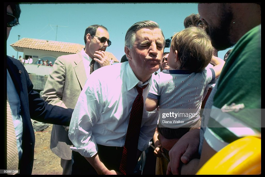 Ex-VP Walter Mondale puckering up, about to kiss parent-held little boy, campaigning for Dem. pres. nomination.