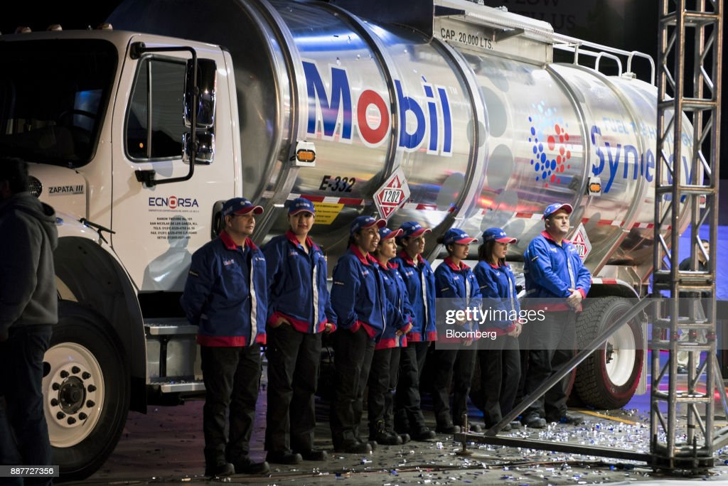 Exxon Mobil Corp. employees stand in front of a fuel tanker during the unveiling of an Exxon Mobil Corp. gas station in Santiago de Queretaro, Mexico, on Wednesday, Dec. 6, 2017. Exxon Mobil Corp. is joining Chevron Corp. and other U.S. refiners to supply the newly free Mexican fuel market. Exxon Mobil indicated Wednesday that it will open 50 service stations by the end of first quarter and invest more than $300 million in Mexico's energy sector. Photographer: Jonathan Levinson/Bloomberg via Getty Images