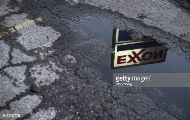 Exxon Mobil Corp signage is reflected in a puddle at a gas station in Nashport Ohio US on Friday Jan 26 2018 Exxon Mobil Corp is scheduled to release...