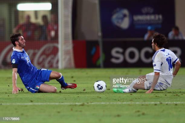 Eyal Golasa of Israel slides into Riccardo Saponara of Italy before being sent off during the UEFA European U21 Championship Group A match between...