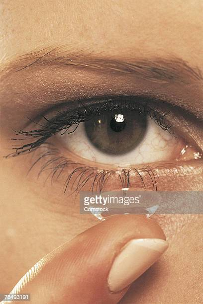 Eye and finger of woman with contact lens