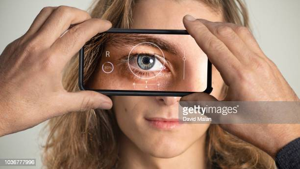 eye being scanned on a mobile device. - retinal scan stock pictures, royalty-free photos & images