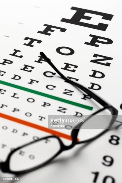eye chart and reading glasses - eye test chart foto e immagini stock