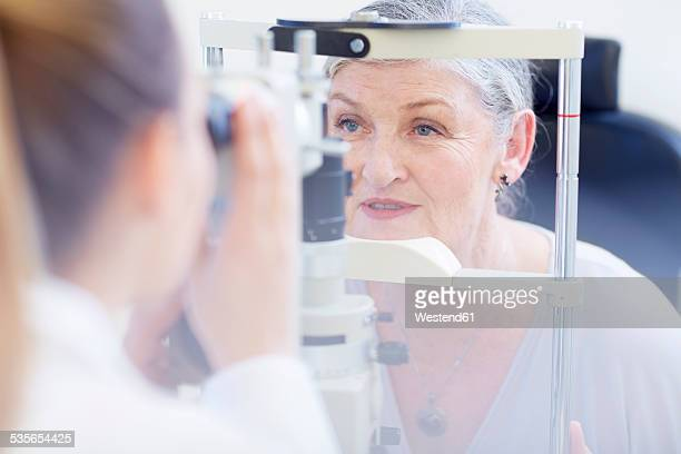 eye doctor examining senior woman's vision - eye test stock pictures, royalty-free photos & images