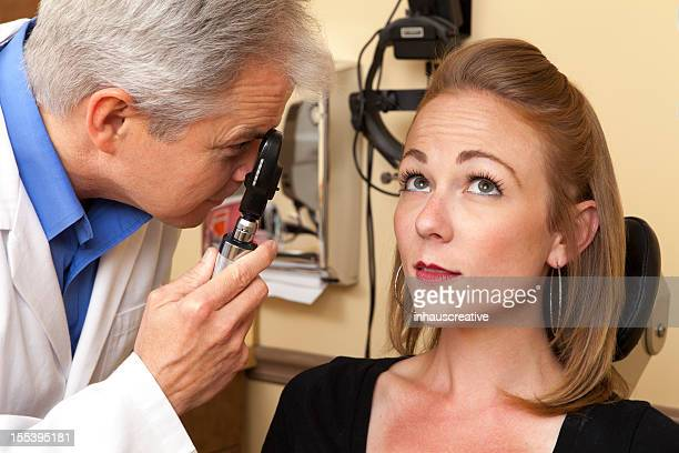 Eye doctor using an ophthalmoscope on a female patient