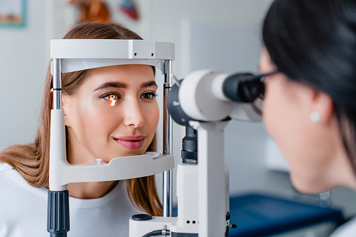 Eye doctor with female patient during an examination in modern clinic 1189362136