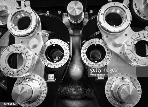 eye exam - lens optical instrument stock pictures, royalty-free photos & images