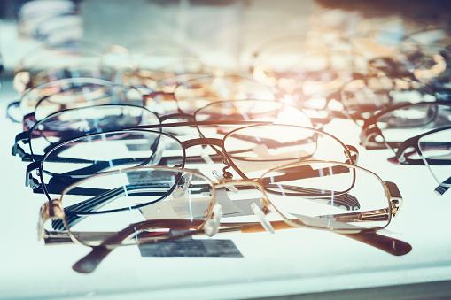 Eye glasses on window display shelves in optics store 905882628
