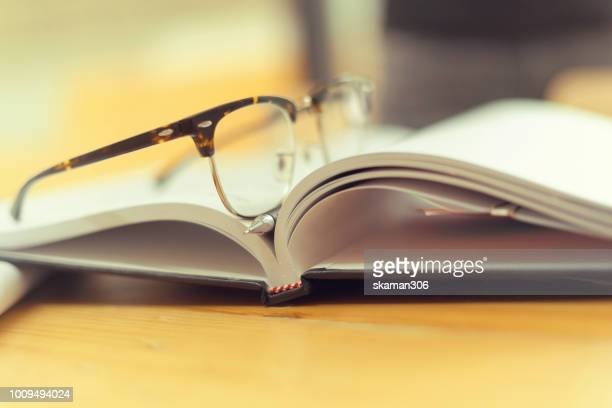 eye glasses with pencil on middle of opened student book