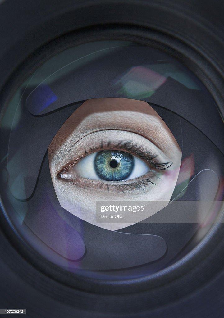 Eye looking through aperture ring of camera : Stock Photo