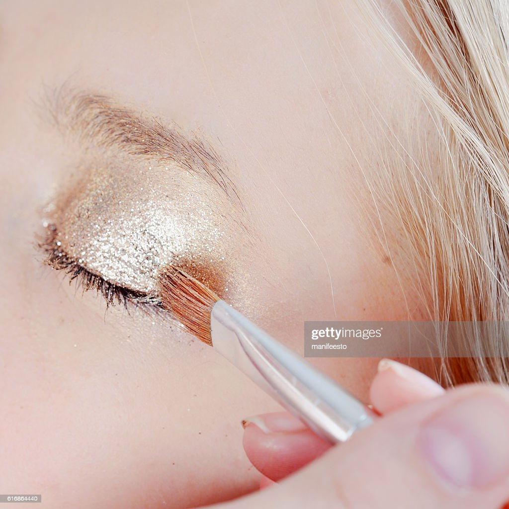 Eye makeup artist applying eyeshadow : Stock Photo