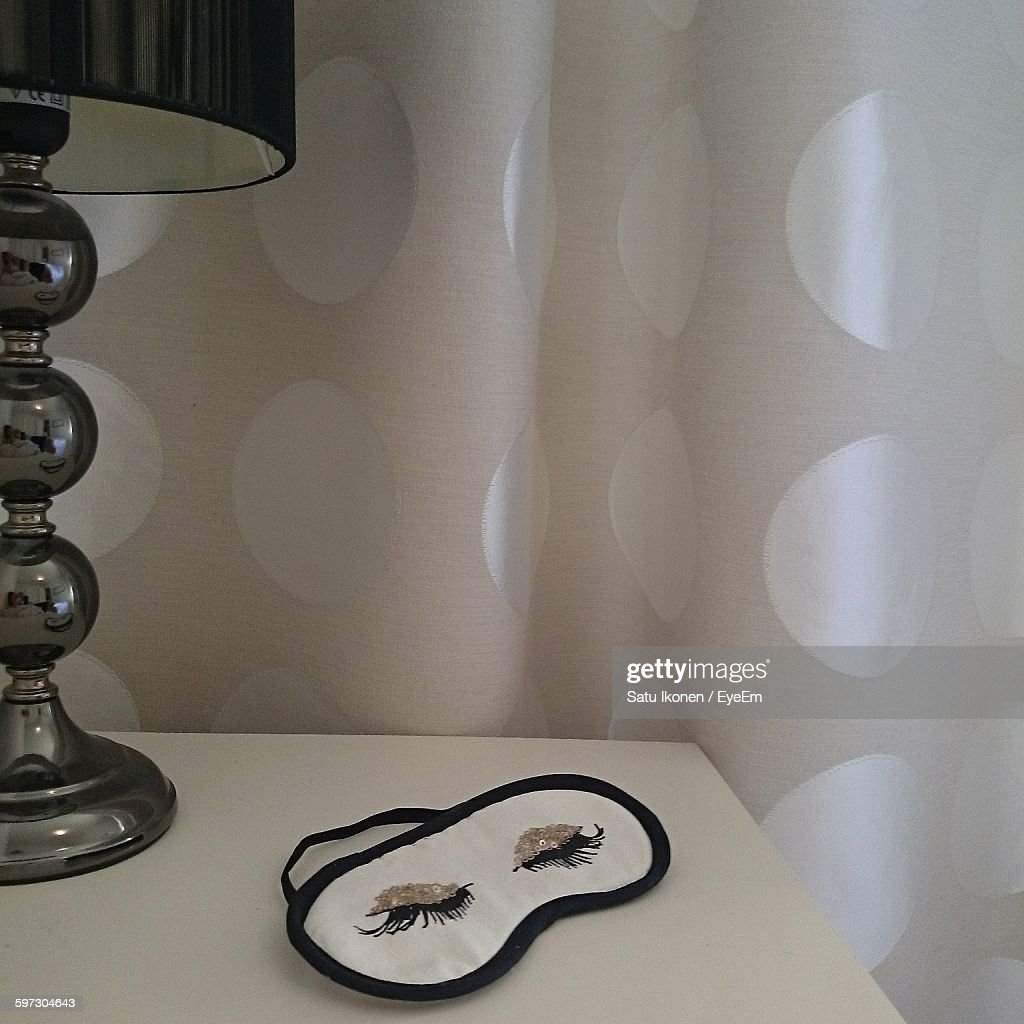 Eye Mask On Table By Lamp Against Curtain : Foto stock