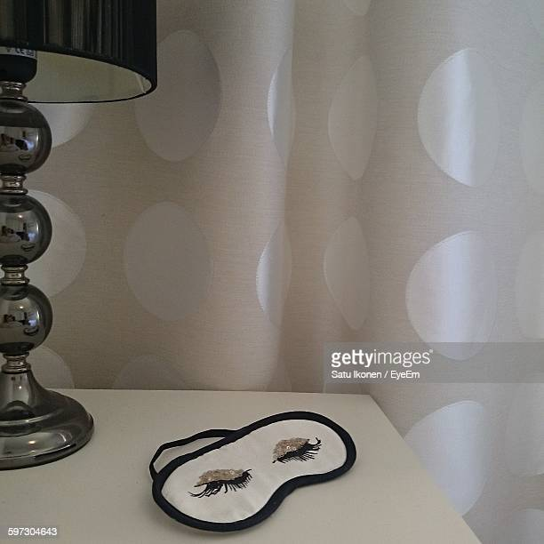 Eye Mask On Table By Lamp Against Curtain