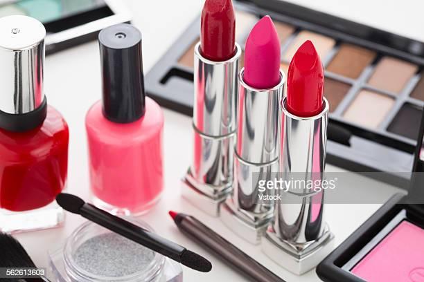 Eye shadow, lipstick and nail polish on table