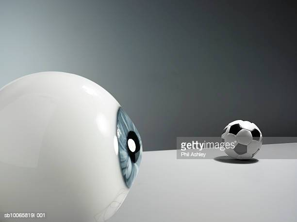 Eyeball and football on white background