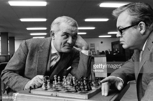Eyeball to eyeball confrontation across the chess board for Clifford Evans left and Patrick Wymark Playing Caswell Bligh and Sir John Wilder...