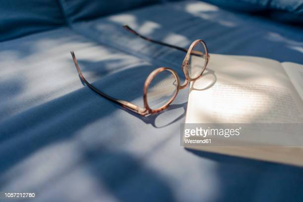 eyeglasses and book lying on couch - sober leven stockfoto's en -beelden